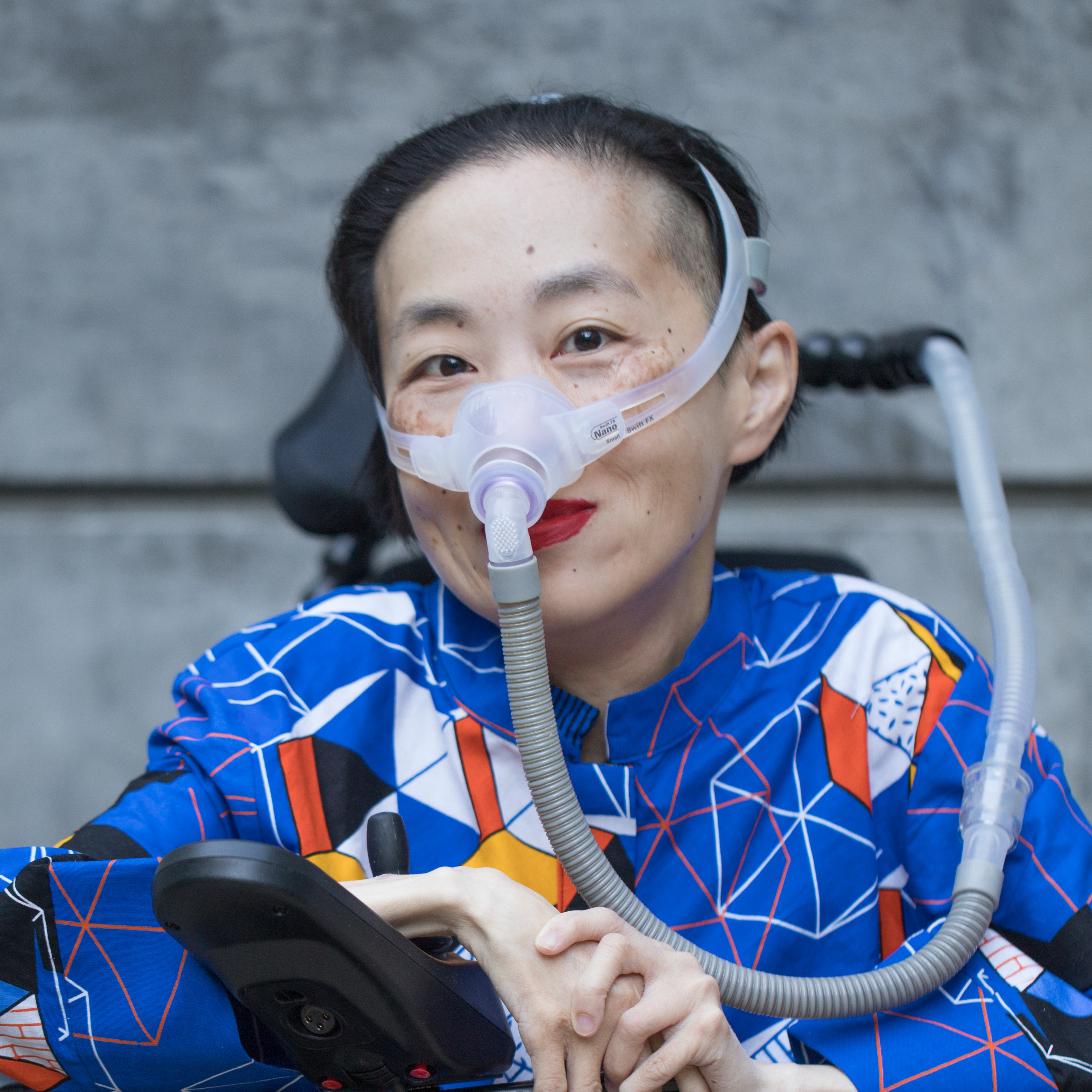 Photo of an Asian American woman in a power chair wearing a blue shirt with a geometric pattern with orange, black, white and yellow lines and cubes; a mask over her nose attached to a gray tube; and bright red lip color. She is smiling at the camera.