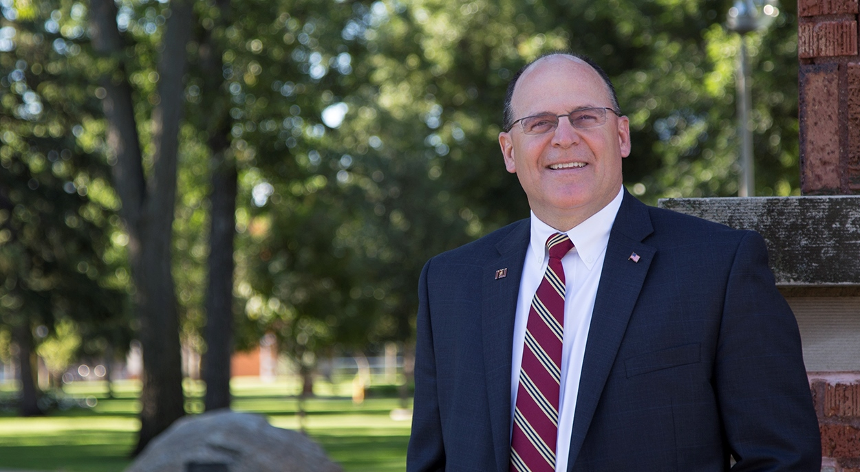 President Tim Downs stands at the campus entrance