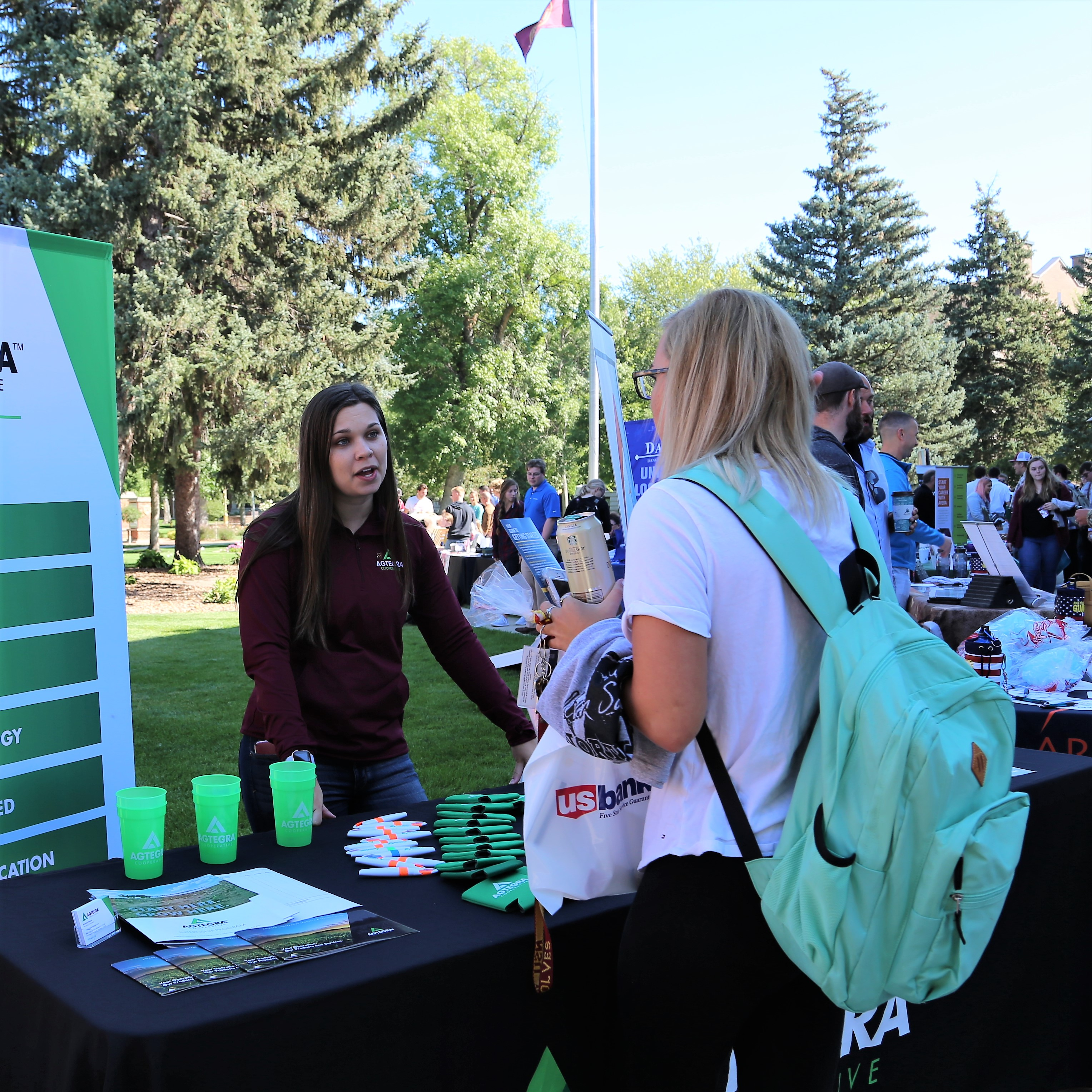 Student talking with employer at job fair on campus green