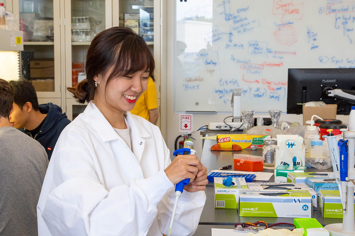 A smiling student works in a Northern lab.