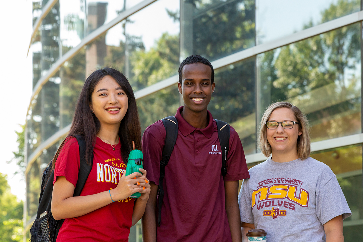 Three smiling students on campus