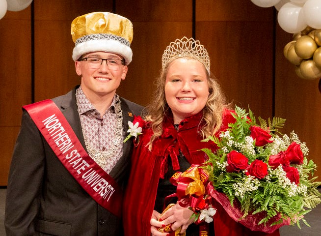 Garret Thompson, marshal, wears a gold crown and sash while Ashley Bruzek, queen, wears a crown and holds a bouquet of roses