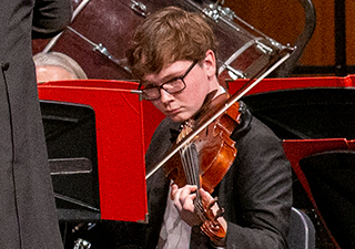 A strings player with glasses performs