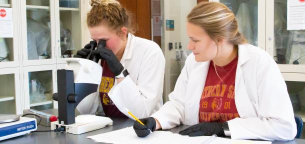 Two female college students in white coats working in a lab