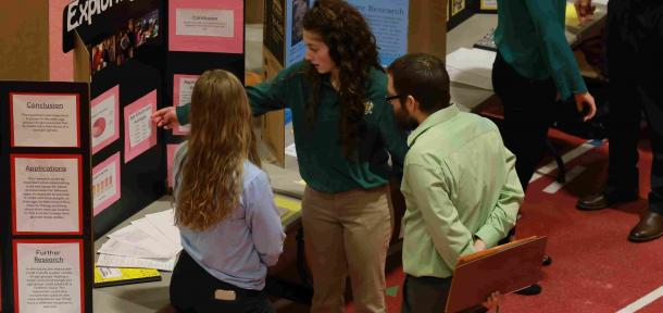 Student showing science project to judges