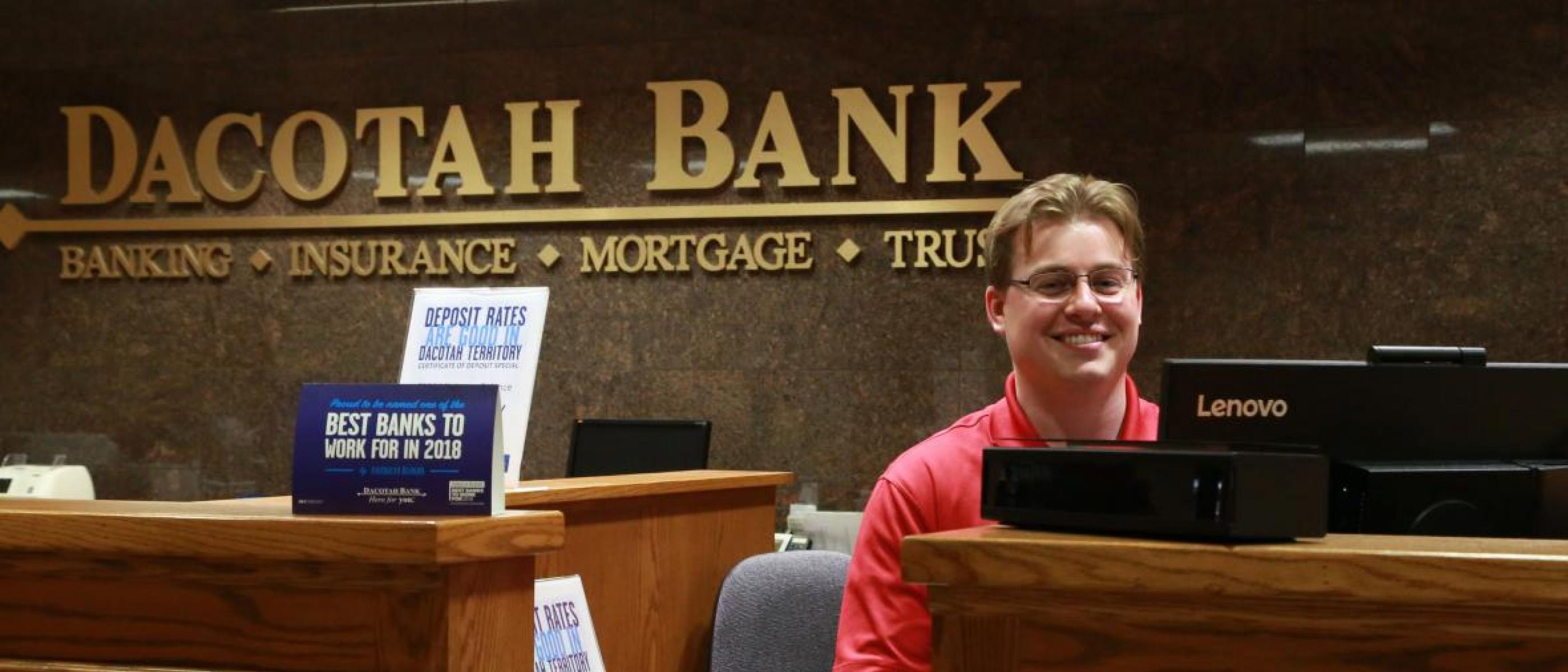 Male bank teller standing in bank