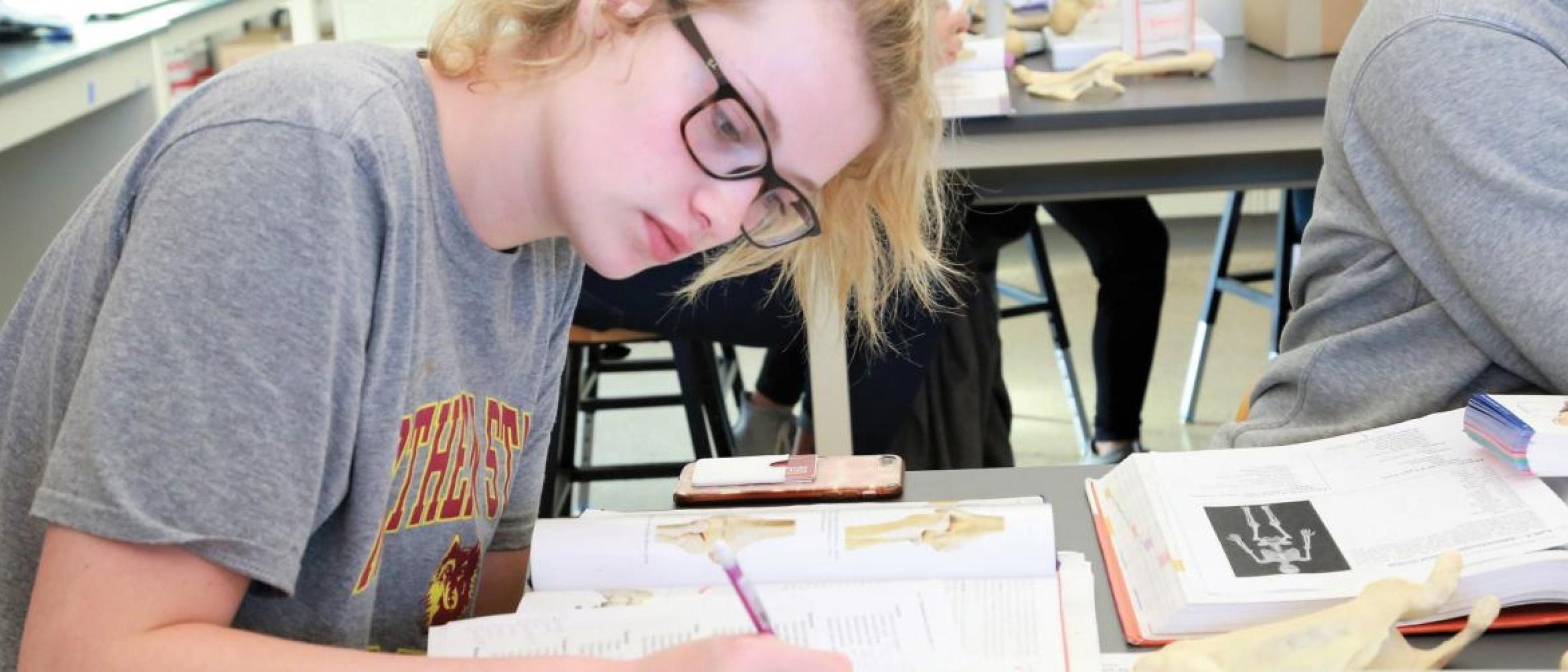 Female student studying from textbook