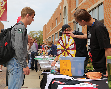 Students spinning a wheel at an outdoor table on campus