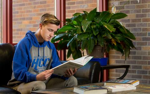 Male student looking at paperwork at Huron Community Campus