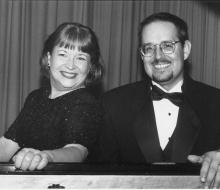 Female and male performer sitting at piano