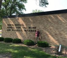 Man standing in front of the South Dakota School for the Blind and Visually Impaired