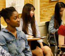 Female students sitting in class listening to a speaker