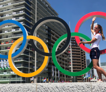 Woman standing by sculpture of Olympic rings