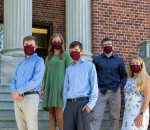 Group of students wearing masks standing on building steps
