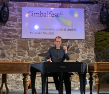 Male student on stage playing the cimbalom
