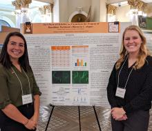 Two female students standing in front of their research poster