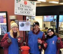 NSU student-athletes standing by Salvation Army Red Kettle