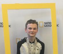 Geographic Bee winner holding frame