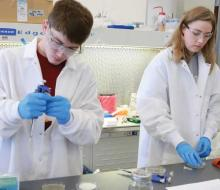 Science students in white coats working in a lab