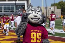 Thunder the Wolf making the NSU Wolf hand signal at the football game