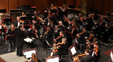 Conductor directing the Aberdeen University-Civic Symphony on stage
